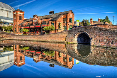 The Malt House  I really like old brick houses. And I really like reflections. So here is a shot with both :). In the shot is the Malt House restaurant (or pub) in Birmingham, UK. In the back there is also the National Indoor Arena.  HDR from three shots, taken with Canon 450D with Sigma 10-20mm lens, handheld.