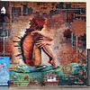 Mural at 501 Macauley Street by Tracie MacVean of a naked woman in the sitting position with an industrial city  sprouting out of her back seen on a wall in Albury in December 2017