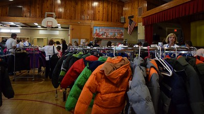 Personal shoppers and students roam the gymnasium in search of the right sizes for the children during Operation School Bell at Alcott Elementary School on Thursday, Oct. 13, 2016.