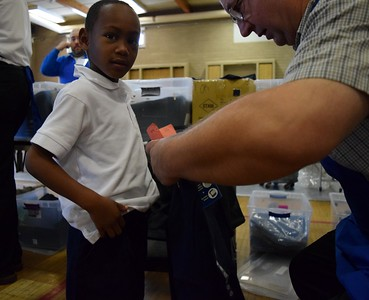 Kemoni Johnson, six, testing the size of his new uniform pants with his personal shopper during Operation School Bell at Alcott Elementary School on Thursday, Oct. 13, 2016.
