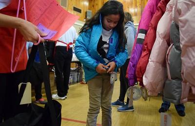 Jasmine Peña De La O, 10, tries on a new jacket during Operation School Bell at Alcott Elementary School on Thursday, Oct. 13, 2016.