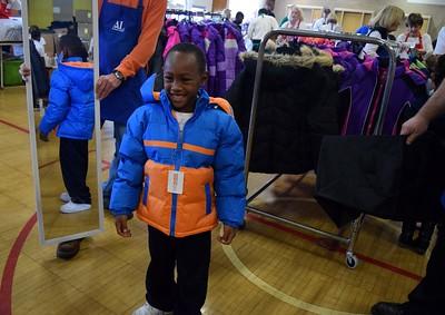 Kemoni Johnson, six, trying on his new winter coat during Operation School Bell at Alcott Elementary School on Thursday, Oct. 13, 2016.