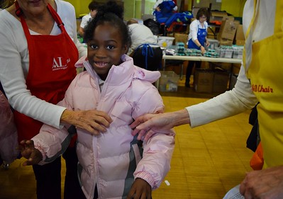Gabrielle Cooley, seven, trying on her new winter coat during Operation School Bell at Alcott Elementary School on Thursday, Oct. 13, 2016.