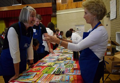 Carol Murphy (left), vice president of philanthropy for the Assistance League of Southeastern Michigan and Sherry Sellinger, a volunteer through the Assistance League, talk children's books during Operation School Bell at Alcott Elementary School on Thursday, Oct. 13, 2016.