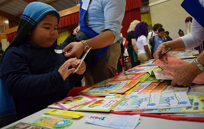 Devin Cantley, six, picks out a new book and bookmark during Operation School Bell at Alcott Elementary School on Thursday, Oct. 13, 2016.