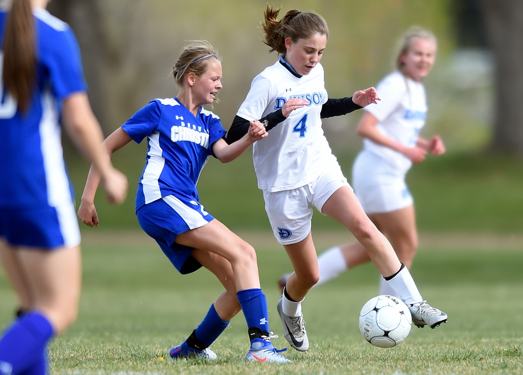 . Alexander Dawson School\'s Kaitlyn Day moves the ball past Grace Phillips during a game against Denver Christian on Thursday in Lafayette. More photos: www.BoCoPreps.com Jeremy Papasso/ Staff Photographer/ April 20, 2017
