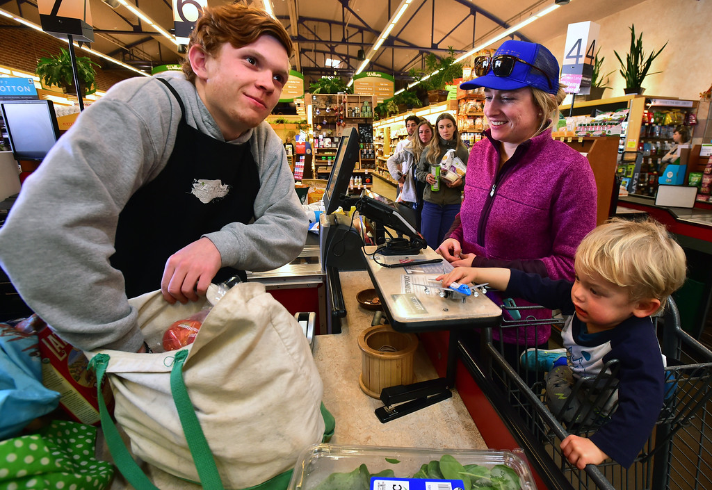 . Checker Evan Kamlet feels at the bottom of the bag for Joy Larkin\'s keys that got covered in groceries as she and her son Trey, 2, check out at Alfalfa\'s Market in Boulder on Monday. For more photos go to dailycamera.com. Paul Aiken Staff Photographer Nov 13, 2017