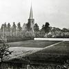 F0026<br /> Bollenland met links het witte huisje aan het Kuipershofje, bewoond door Spierenburg. In het midden de Ned.-herv. kerk (Dorpskerk). Verder is het grote pand van Melman te herkennen en de schuur en huisjes achter schilder Van Goeverden. Rechts de voormalige herv. pastorie, vanaf 1968 in bezit van de fam. Langeveld. Geheel rechts (nog gedeeltelijk zichtbaar) het huis van Verdoes, nu de woning van S. Vliem. Tussen het bollenland en het kerkhof liep de Hortuslaan. De witte muur is de afscheiding van het erf van (tegenwoordig) Vliem en het bollenland van Oostveen. Op het bollenland tegen de witte muur is later de Hervormde School gebouwd, die in 1930 in gebruik is genomen.  Foto: eind jaren twintig.