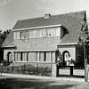 F1187 <br /> In 1930 kocht dhr. Van der Laan, politieagent te Sassenheim, deze twee huizen aan de WillemWarnaarlaan, nrs. 21 en 23. Het linker huis werd verhuurd, het rechter bewoonde hijzelf. Op de foto staat dhr. Van der Laan met dochtertje Annie, mevr. Van der Laan met dochtertje Tilly op de arm en zoon Arjen naast haar. Foto: ca. 1930.