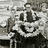 F2185<br /> Dhr. A. Wolvers verkoopt bloemenslingers bij de Warmonderdam. Hij wordt vergezeld door zijn twee  kinderen (zoon Gerard of Gerrit en dochter Riet).