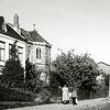 F0458a <br /> Huize West End met schuin erachter het Annaklooster aan de Hoofdstraat. Huize West End is gebouwd in 1834. G. Verschoor schrijft dat de naam 'West End' duidt op het westelijke einde van het centrum van de gemeente. Tot zover deed de klapwaker zijn nachtelijke ronde. Van 1870 tot 1887 was West End de pastorie van de r.-k. kerk. De heer P. van Deursen heeft er van 1911 tot 1938 gewoond. Daarna bewoonde de fam. Schinck de villa. Nu in 2016 staat het pand al 20 jaar leeg en is in erbarmelijke staat.