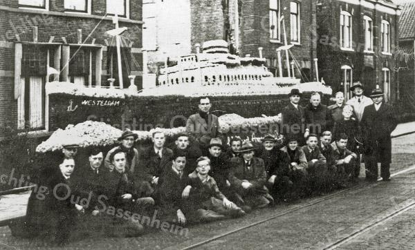 F1082 <br /> In de tijd van het eerste bloemencorso in 1948 werd het stoomschip 'Westerdam' uitgebeeld. Het bouwwerk is met hyacinten en narcissen bedekt en is gemaakt door de fa. Dijkstra in opdracht van de Holland-Amerika Lijn. Het staat hier opgesteld op de Hoofdstraat bij de ingang van de Molenstraat.