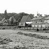 F3962<br /> Het stuk land achter de Kerklaan, we zien de huizen op de achtergrond. Rechts staan de huizen van de Bijweglaan.  In het midden de christelijk-gereformeerd kerk, die in 1926 in gebruik werd genomen – nu is het de Havenkerk. De foto is ongeveer genomen vanaf het punt waar later de Oosthavenbrug over de Sassenheimervaart werd gebouwd. Op het braakliggende terrein zijn in de jaren vijftig de huizen Parklaan 57 t/m 95 gebouwd.