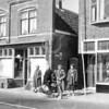 F0713 <br /> De Hoofdstraat in de jaren '50 of '60 in de week van het bloemencorso, gezien de bloemversiering. Links (met vlag) de winkel van kruidenier van Nieuwkoop. Rechts het nieuwe pand van de manufacturenzaak van W. Noordermeer. De dame op de fiets is Cock Verkleij. Nu is sinds 1999 Eetcafé de Voogd in dit pand gevestigd.<br /> Foto: jaren '50 of '60.