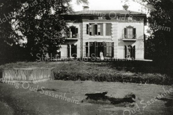 F0441 <br /> Huis Ter Beek stond enkele honderden meters ten noorden van Sassenheim, vlakbij de Beekbrug en bij de H.H. Engelenbewaarderskerk (de Koepelkerk) aan de rechterzijde van de Heereweg. De hofstede moet tussen 1800 en 1830 gebouwd zijn, evenals de boerderij die erachter stond. Bij de deur de vrouw des huizes mevr. Vanger. De foto is gemaakt door H.L.F. Vanger. In 1909 (nog vóór de bouw van de kerk!) verkochten zij het pand aan de St. Vincentiusvereniging, een bisschoppelijke instelling die zich bekommerde (en bekommert) om het lot van de zwakkeren en kwetsbaren in de samenleving. Huis Ter Beek werd een gezinsvervangend tehuis met de naam St. Vincentiushuis, dat heeft bestaan tot begin jaren '80. Het pand is in 1988 afgebroken om plaats te maken voor de bouw van de woonwijk Ter Beek. Foto: 1906.