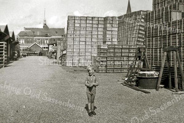 F2419<br /> Kistenfabriek M. Bakker. Een nog  jeugdige Robert-Jan Bakker staat op het opslagterrein van de kisten, met op de achtergrond de Julianakerk.  Foto: 1956.