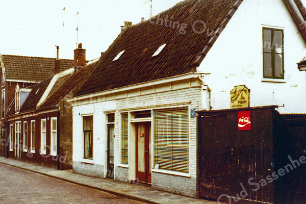 F0294 <br /> Het huis en de winkel van G. van Egmond, poelier en handelaar in wat kruidenierswaren en in snoep, ijs en frisdranken aan de Kerklaan. In de jaren '60 heeft een van de zoons van Van Egmond ook nog een aantal jaren een snackbar gerund in dit pand. Na het overlijden van zijn ouders heeft zoon Kees de winkel aan de kant gedaan en is alleen met het poeliersvak verdergegaan. Links van het pand de huizen van de fam. Van Duijn, Hogewoning en Oudshoorn, met links daarvan de olieschuur van Jac. Oudshoorn. Al deze panden zijn gesloopt in 1975. Foto: ca. 1975.