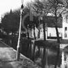 F4029 <br /> Links de Vaartkade en rechts de Kastanjelaan. <br /> Aan de rechter kant vlnr: het oude huisje waar Van Tol woonde; de witte boerderij van Karel Drost en het witte huis van de fam. Postma. Foto: jaren '50