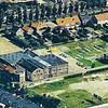 F3915<br /> In het midden van de foto staan de molen en de bedrijfsgebouwen. Rechtsonder een klein stukje Koetsiersweg en links een deel van de Diligence. Bovenaan ligt de Zandsloot en rechtsboven zijn de huizen van de Postwijkkade en de Oude Poststraat goed te zien. Foto: circa 1985.