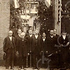 F4352<br /> De foto is genomen tgv van het 25-jarig regeringsjubileum van koningin Wilhelmina. Locatie: Hoofdstraat vóór de vroegere Keerweerlaan tussen de slagerijen Hulsbosch en Couvée. De tweede man van links is Jan van der Ploeg en de tweede van rechts is zijn broer Engel van der Ploeg. De bijnaam van de broers was 'Strik en Stropdas'. In het midden (met snor) staat dhr. Bosma. Naast hem staat Jan Herruer. De derde man van rechts is Piet Hoogeveen.<br /> De bewoners van de Keerweerlaan waren: nr.1: Bosma; nr.3: Heemskerk; nr. 5: van Diest; nr. 7: Ploeg-Beijk; nr. 9: van Leeuwen; nr. 11: van der Ploeg; nr. 13: P. Schrama; nr. 15 nb; nr. 17: H. Herruer en nr. 19: P. Hoogeveen.
