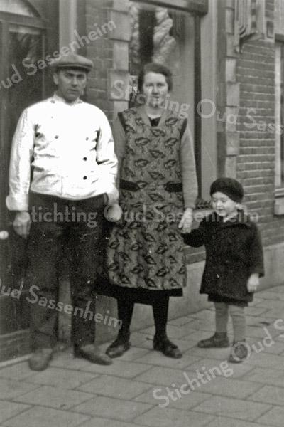 F0572 <br /> Bakker Barnhoorn met zijn vrouw en hun dochterje Cobie voor de deur van de winkel, Hoofdstraat 185. Foto: ca. 1938.