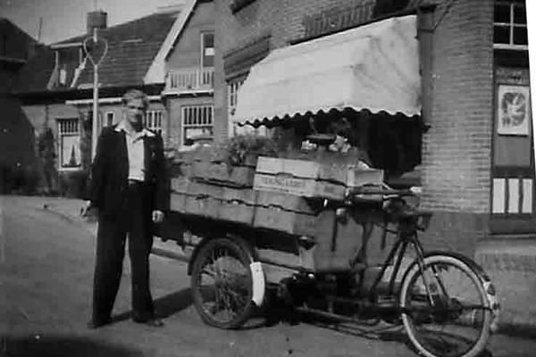 Fcs0426<br /> Ben Schreuder als groenteboerknecht. Op de achtergrond de winkels van fotograaf Turk en snoephandel van Kees van Diest.