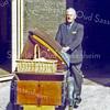 F0573 <br /> Bakker Barnhoorn, klaar om te vertrekken met zijn bakfiets met brood. Hij komt uit de poort tussen de panden waar nu in 2016 de winkels van Duynstee en van Landwer Johan zijn gevestigd. Foto: 1960.