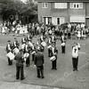 F0993 <br /> Een optreden van Adest Musica vóór Parklaan 33, ter gelegenheid van de priesterwijding van C.J. van der Voort op 31 mei 1958. Op het huis van dhr. Lanser staat een T (telefoon). Tijdens de oorlogsjaren had hij een telefoonaansluiting vanwege zijn beroep. Foto: 1958