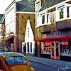 F0284 <br /> De Hoofdstraat in het centrum aan de westkant. Rechts de kruidenierswinkel van Cor van Goeverden, in 1986 overgenomen door fa. De Jong, handel in lederwaren. Later werd het boekhandel Bruna en nu (2016) is het The Read Shop. Foto: 1979.