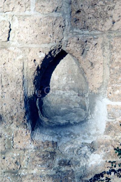 F0101 <br /> Nisje voor wijwater naast de zijdeur van de  Ned.-herv. Kerk of Dorpskerk. Vroeger stond er een portaal voor en diende dit nisje voor rituele reiniging bij het binnengaan van de kerk. Het is in 1971 onder het klimop vandaan gekomen en in gerestaureerde staat voor het nageslacht bewaard gebleven. Foto: 1998