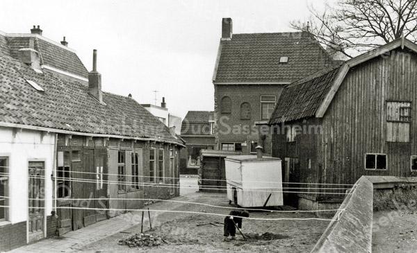 F0033 <br /> Het Kuipershofje (gesloopt in 1959), een oud buurtje tussen de Hortuslaan en het kerkhof van de Ned.-herv. kerk (Dorpskerk). Het Kuipershofje is genoemd naar Piet Schrama, die daar omstreeks 1880 zijn kuiperij had. Rechts de tabaksschuur uit 1872 van de sigarenfabrikant Dirk Koning, in het begin van de 20ste eeuw gebruikt als opslagplaats van de olieboer Oudshoorn. Links de klompenmakerij van Groeneveld, achter de schuifdeur. De witte kar naast de schuur is de toen nog mobiele 'Snackbar Thomas'. De waslijnen waren gemakshalve aan de kerkhofmuur vastgemaakt. Op de achtergrond het hoge pand van kapper De Jong en verder naar achteren de winkel van Faas aan de Hoofdstraat. Zie ook Sassenheim in oude ansichten van G. Verschoor, pag. 52.   Foto: 1959