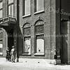 F2748<br /> Mevrouw Lascaris (rechts) staat vóór het voormalige doktershuis van dokter Hueber. In 1956 is dit pand verbouwd tot winkel in huishoudelijke artikelen enz. voor de fa. G. Lascaris, Hoofdstraat 201.