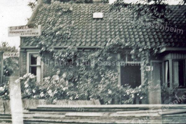 F0177 <br /> Het huis van C.J. Melman aan de Vaartkade 11. Links een bord met het opschrift: 'C.J.Melman, timmerman en aannemer'. Op de voorgrond ligt timmerhout opgeslagen. De asschuur (die vlakbij stond) diende toen nog als brandweergarage. De heer Melman was ook lid van de brandweer. Aan de achterzijde was de werkplaats van het timmerbedrijf gevestigd. Foto: 1937.