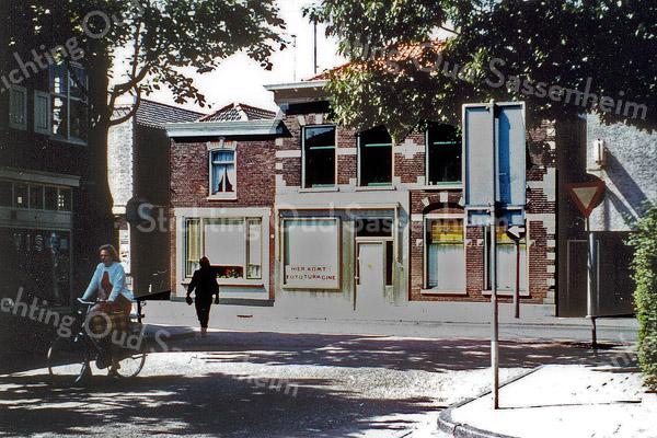 F0281 <br /> De kruising J.P.Gouverneurlaan/Hoofdstraat, links de viswinkel van Nic.Roos waar nu (2016) Assurrantiekantoor Bijdorp en makelaar De Leeuw gevestigd zijn. Aan de overkant van de Hoofdstraat links het woonhuis van J. Verkleij, voorheen winkel in kruidenierswaren, en boter, kaas en eieren. Daarnaast winkel en woonhuis van bakkerij Barnhoorn, in 1972 verkocht aan Leo en Kees Turk die er hun fotozaak Turk Cine vestigden. De fotozaak is er nog steeds, nu gedreven door Kees' zonen Rob en Fred.  Opa G.C. Turk was in 1927 met de fotozaak begonnen in de Charbonlaan. Foto: 1972.