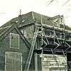 f3196<br /> In de jaren '50-'60 is het pand (in de steigers) de jongerensociëteit 'De Stormbal' geweest. Wat vroeger de functie van het gebouw is geweest is niet bekend. Later werd het gebruikt voor de Moskee voor de Islamitische Gemeenschap. Links daarvan pand staat de asschuur (beide panden zijn gesloopt in 2002). Foto: 1957