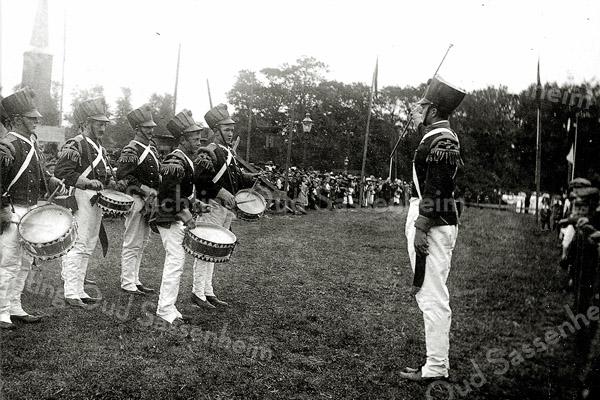 F1137 <br /> Feestelijke herdenking 1813-1913, het onafhankelijkheidsfeest. Het tamboerkorps, verkleed als Franse soldaten. Op de achtergrond de toren van de Ned.-hervormde kerk. De Onafhankelijkheidsfeesten werden gehouden op woensdag 17 en donderdag 18 september 1913. Deze foto is genomen op het feestterrein op De Overplaats.