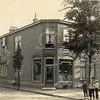 F0775 <br /> Op de hoek van de Bijdorpstraat staat dit pand dat in 1909 werd gebouwd voor bakker J. Stelma. Later zaten in dit pand Autobedrijf Broertjes en Autobedrijf Beugelsdijk. Behalve voor kinderen als stoffering van het plaatje had de fotograaf ook oog voor mensen op de ladder. Foto: vóór 1921. <br /> <br /> [Collectie Oudshoorn 056: broodbakkerij J. Stelma 1909].