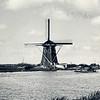 F0353 <br /> De Poelmolen aan de ringvaart in de Roversbroekpolder. Een goed onderhouden molen, die jaren geleden weer geheel is gerestaureerd. Op de achtergrond rechts van de molen de St. Agathakerk van Lisse. Foto: 1959.