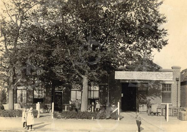 F0769 <br /> Het woonhuis en bloembollenhuis van D. van der Voort, die beide in 1902 werden gebouwd. Dit pand aan de Zandslootkade nr. 14 is in 1981 afgebroken. Ook hier zien we kinderen voor de stoffering van het beeld. Foto: vóór 1921.<br /> <br /> [Collectie Oudshoorn 029: woonhuis en bloembollenhuis D. v.d. Voort 1902. Zandslootkade 14 (pand van Van der Geest, afgebroken in 1981).]