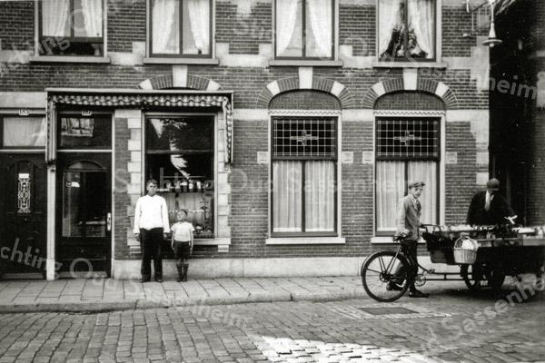 F0117 <br /> De winkel en rechts daarvan het woonhuis van de fam. Barnhoorn. Een bakkerij van de oude stempel, waar een voormalig kamerraam als etalage dient. Het pand stond op de plaats waar nu (2016) Fotoservicewinkel Turk b.v. is gevestigd. Op de foto staat vader Barnhoorn met zoon Bram voor de winkel. De Hoofdstraat is nog met 'kinderhoofdjes' geplaveid en rechts zien we een jongen van Van Dijk (?) van de Gouverneurlaan met een bakfiets. Foto: ca 1932.
