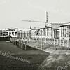 F3168<br /> Op deze foto uit 1979 zien we de houten schoolbarakken van het Rijnlands Lyceum Sassenheim (RLS) aan de Van Alkemadelaan, waarvan de eerste zijn geplaatst in<br /> 1972. De barakken zijn in 1995 vervangen door een nieuw groot stenen schoolgebouw, dat in 2007 werd uitgebreid. Door zijn unieke driehoeksvorm kreeg dit nieuwe gebouw ook een plaatsje in Madurodam.<br /> Foto: het 'binnenhof met geitenhok' (collectie dhr. C. Pieterse).