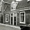 F0084 <br /> Woonhuizen aan de Kerklaan, vlak voordat deze werden gesloopt. Links de vroegere wagenmakerij Bakker. Aan de kant van de Boschlaan zat een 'eerste steen' ingemetseld (door ene Bakker). Later heeft dit pand dienstgedaan als olieschuur van Jacob Oudshoorn voor de maatschappij De Automaat. Daarnaast het woonhuis van Oudshoorn, na diens overlijden bewoond door ene Müller. Het rechterwoonhuis is jaren bewoond geweest door de fam. Hogewoning, het laatste jaar door Gerrit de Bruin. Op de huizen zit al het bordje 'onbewoonbaar verklaarde woning'. Foto: 1975.