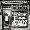 F2154<br /> Het Boter & Kaashuis van Jan Eikelenboom aan de Floris Schoutenstraat nr. 5 in 1933. In 1939 verhuisde de zaak naar de hoek Floris Schoutenstraat/Hoofdstraat waar het bedrijf werd voortgezet tot 1979.  Daarna kwam in dit pand de melkzaak van Jac. van Rijn. Thans (2016) is hier een kapsalon in gevestigd.