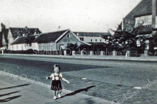F0083 <br /> 'De Zevenhuizen', gelegen aan de Hoofdstraat. Een oud, vervallen buurtje van arbeidershuisjes, die kort na het maken van deze foto gesloopt zijn. Het huis met het rieten dak en de huizen op de achtergrond staan er nog steeds. Het kindje is Arda Visscher,  geb. 23-3-1951. De bewoners van de Zevenhuizen zijn: fam. Van der Lans; fam. Toom; fam. Hubers; fam. De Waard; fam. Kulk (zij hadden twee huizen waarvan één voor de mandenmakerij) en de fam. Vonk. Foto: 1952.