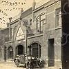 F0783 <br /> Dit pand aan de Hoofdstraat werd in 1906 in jugendstil gebouwd als winkel en garagebedrijf van H.J. Uphoff, later voortgezet door Van Werkhoven.  Later kwam hier een dierenwinkel en nu is in dit pand Lingerie Melman gevestigd. Let eens goed op de prachtige tegeltableaus die helaas deels werden overgeschilderd, maar later weer in oude glorie zijn hersteld. Vóór het pand staan twee jongetjes te poseren voor een schitterende open tweezitter, een Dodge uit 1920 met nummer H 8317. Foto: 1920.<br /> <br /> [Collectie Oudshoorn 052: winkel en garage H.J. Uphoff 1908 - Werkhoven.]