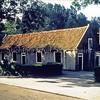 F0055 <br /> Boerderij van N. Breedijk aan de Menneweg 20. De stal heette 'het Wespennest' en bestond oorspronkelijk uit 4 huizen, waarvan de tussenmuren later werden weggebroken. Rechts naast de boom is boer N. Breedijk te onderscheiden. Bij mevr. Elst aan de Hooge Wei hangt een schilderij van dit tafereel van de hand van J. Hogewoning. Foto: 1989.