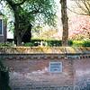 F0503<br /> De kerkhofmuur van de Ned.-herv. kerk of Dorpskerk in de lente met een weelderige begroeiing . De ringmuur is in 1988 gerestaureerd, zie ingemetselde steen. Foto: 1999.