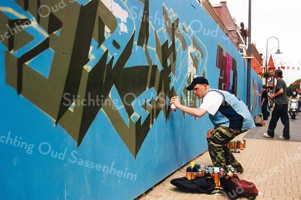 F2598<br /> Het beschilderen van de schutting aan de Hoofdstraat. Foto: 2004