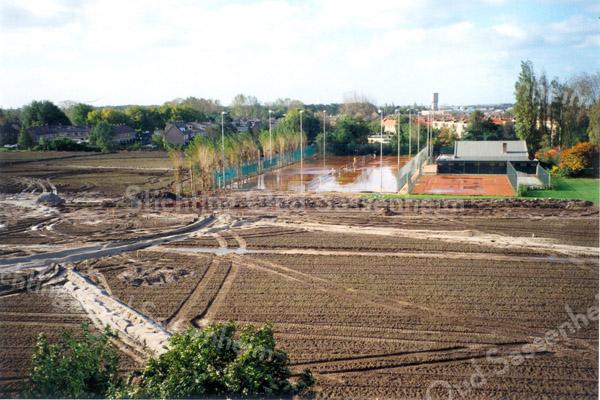F0129 <br /> Het terrein, waar de nieuwe woonwijk 'Mennepark' gebouwd zal worden. Het voormalige terrein van rugbyclub 'The Bassets' op de voorgrond en links het voormalige voetbalterrein. Op de achtergrond de tennisbaan en in de verte de watertoren. De foto is genomen vanuit de flat van Dick van Leeuwen op de 5e verdieping van 'Parkhove'. Foto: 1997