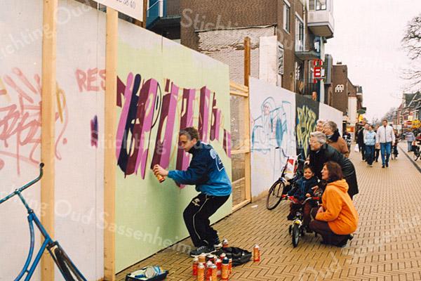 F2512<br /> Graffitikunstenaars aan de slag op de bouwschutting tussen de Hema en de Etos aan de Hoofdstraat te Sassenheim. Foto: 2003